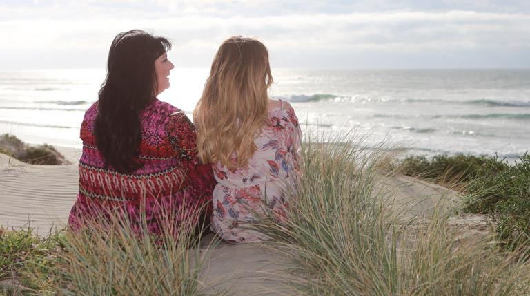 Annette Gregory sitting on beach with daughter Baylee