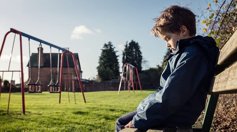Boy sitting alone on playground bench - bullying is a common problem for children with hemophilia