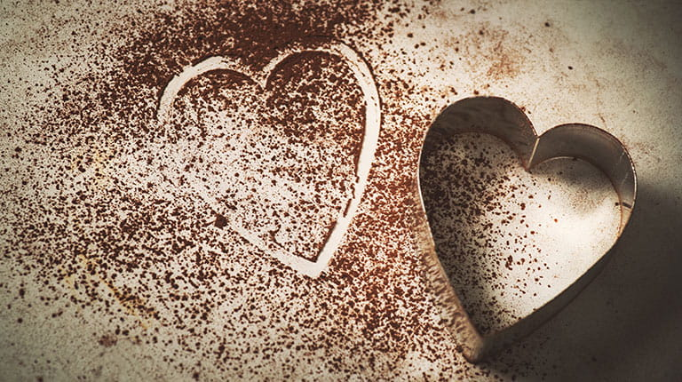 Heart-shaped cookie cutter next to outline of heart in cocoa dust