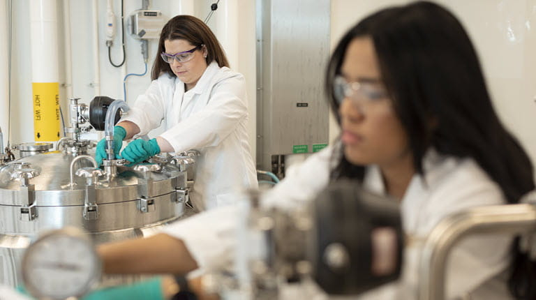 Two women work in biotech manufacturing