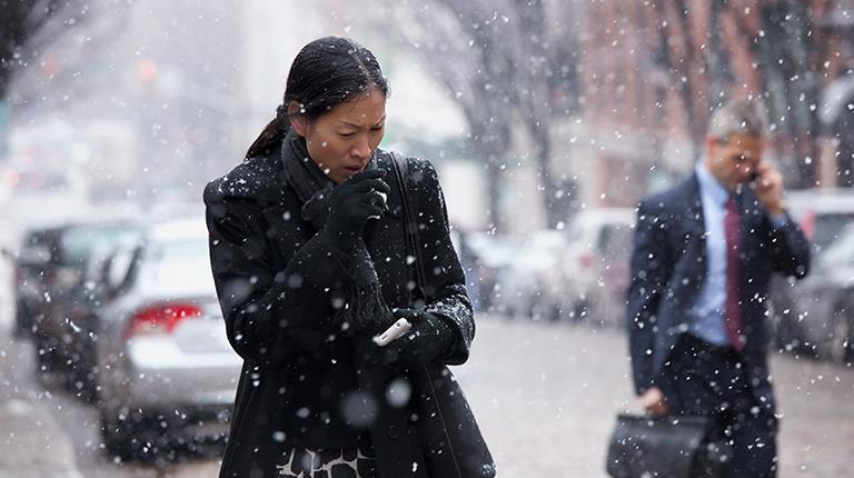 Woman coughing while walking along a snowy city street