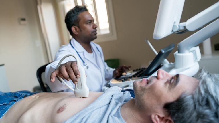 Doctor performing ultrasound test on man
