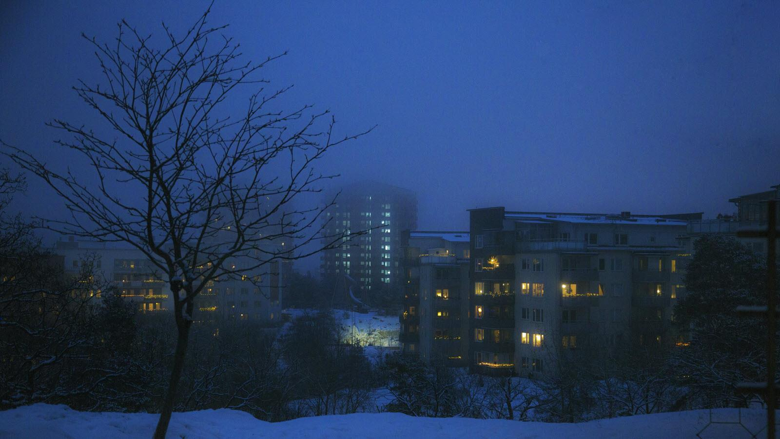dark winter afternoon with lights glowing in an apartment building