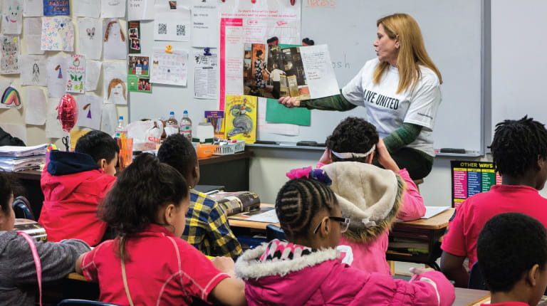 Marlene Gregory, Regional Sales Manager, CSL Behring, reads to a group of students at Gotwals Elementary School in Norristown, Pennsylvania, as part of a charitable partnership between the United Way of Greater Philadelphia and Southern New Jersey and CSL Behring. Employees like Marlene say they enjoy participating in activities such as these throughout the year, and experts agree that there are multiple benefits to both community organizations and businesses that encourage their employees to volunteer. (Photo/Peter Chung/United Way of Greater Philadelphia and Southern New Jersey)