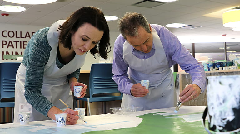 CSL Behring employees painting part of a mural illustrating the promise of biotechnology