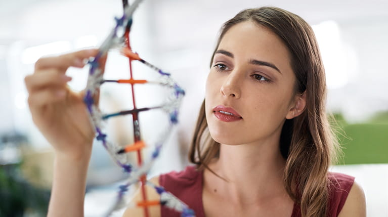 Woman looking at DNA helix model