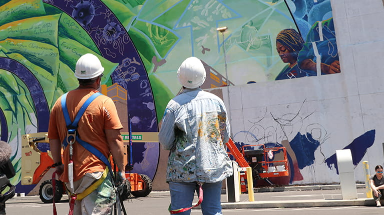 Artists looking at unfinished biotechnology mural in Philadelphia, host of BIO2019