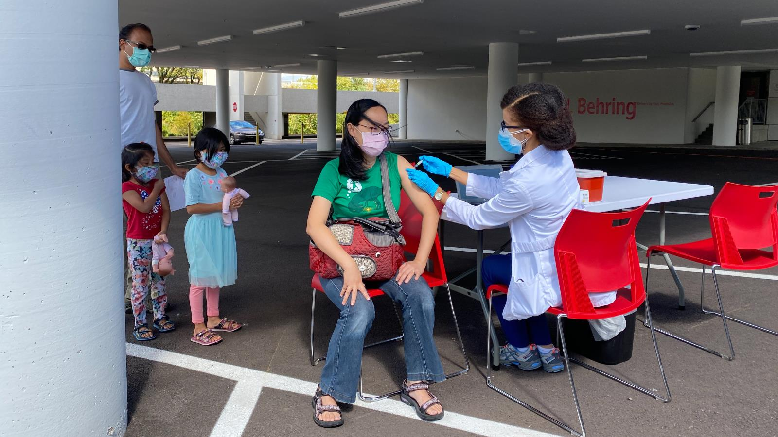 Dad and two daughters wait while their mother gets a flu shot outside.