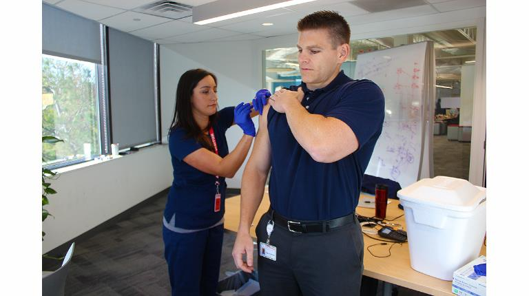 CSL Behring Group Manager, Finance, Troy Kukorlo receives a vaccination from Registered Nurse Meredith Bruno. Hundreds of employees at CSL Behring's site in King of Prussia, Pennsylvania, made sure they took advantage of free flu shots offered by the biotech leader.