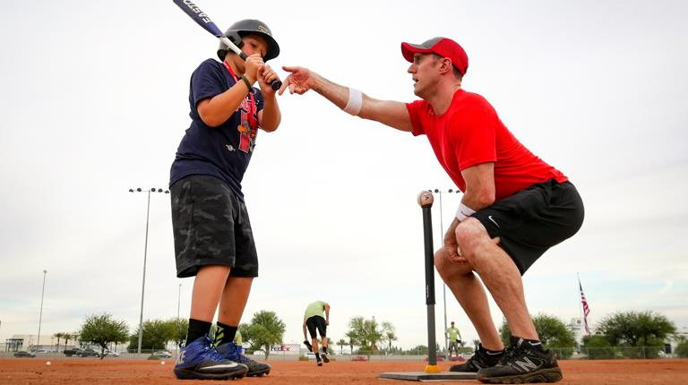 Baseball coach giving young batter tips on hitting
