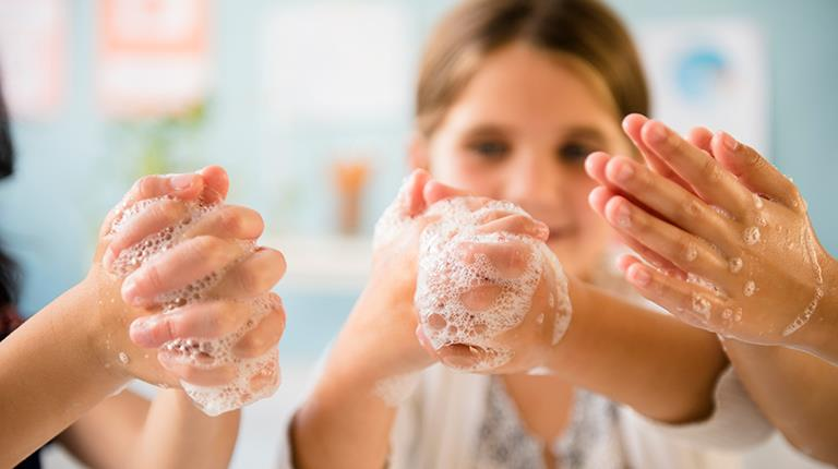 Children holding up soapy hands