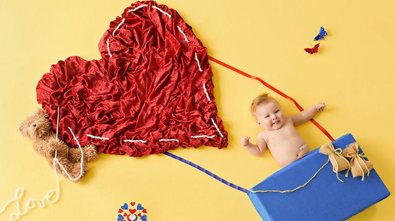 Baby posed to appear to be floating in a crafty heart-shaped hot air balloon.