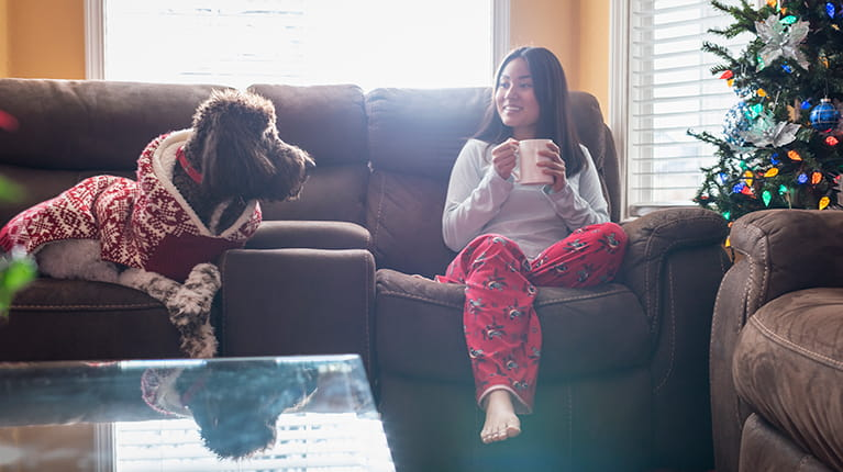 Woman sitting on couch with pet dog near Christmas tree