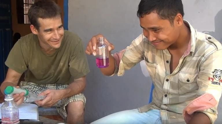 Lukas with his friend Makara, who accompanied Lukas to the children's homes, testing the water for its purity.