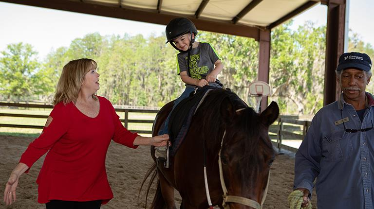 Von Willebrand disease patient Mary Ann Massolio leading a child during a horse riding lesson.