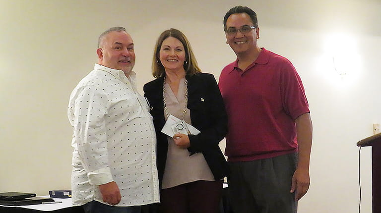 Bob Robinson, Executive Director of BDAI, (left) and Daniel Contreras, BDAI Board President (right) with Maureen Powell, who accepted the Outstanding Support Award on behalf of the CSL Behring Kankakee employees.