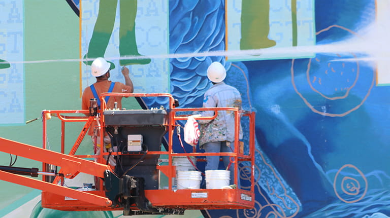 Artists paint a biotechnology mural on a Philadelphia wall