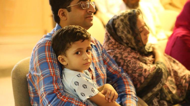 A Pakastani boy and his father listen to a lecture.