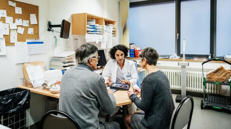 Patients and doctor meet to partner about treatment