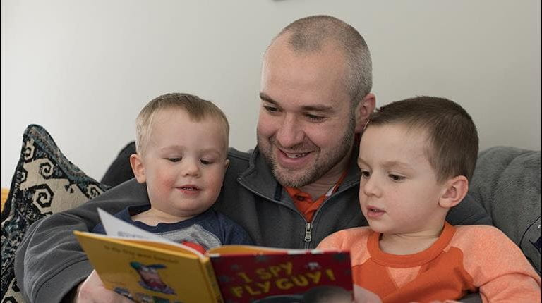 Hemophilia patient Pete Dyson reading a book to his young children