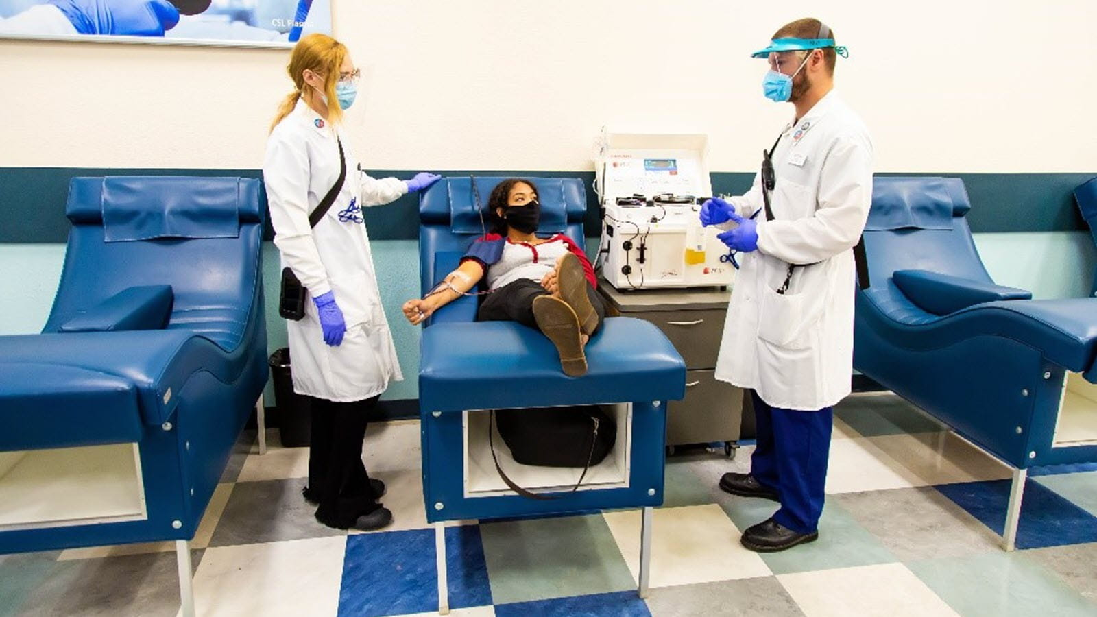 Plasma donor and two CSL Plasma staff members in PPE