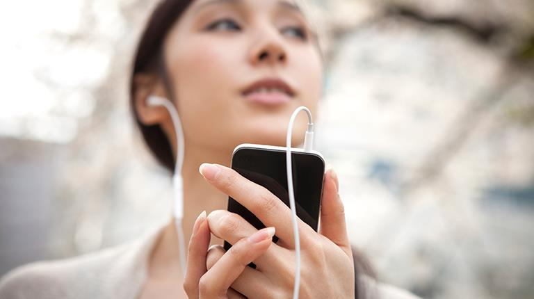 Woman listening to music on smartphone
