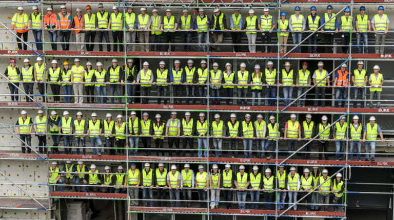 Dozens of workers standing on scaffolding at CSL Behring facility in Marburg, Germany.