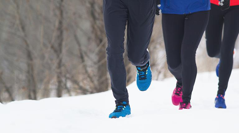 Group of people running in the snow. The New England Hemophilia Association (NEHA) and the New York City Hemophilia Chapter (NYCHC) are launching  a 100-day fitness challenge.