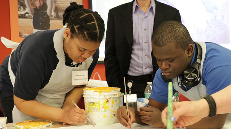 Philadelphia high school students painting part of a mural illustrating the promise of biotechnology