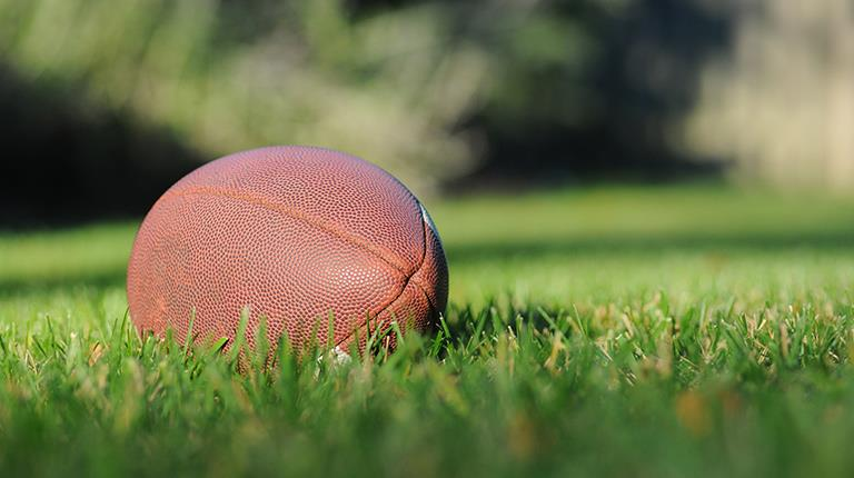 Football pictured on grass field