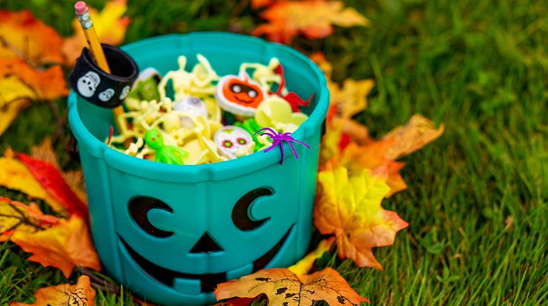Teal pumpkin bucket filled with non-food treats. Teal is the recognized color for food allergy awareness.