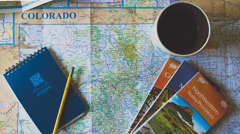 Notebook, pencil, and cup of coffee laid on top of map of Colorado