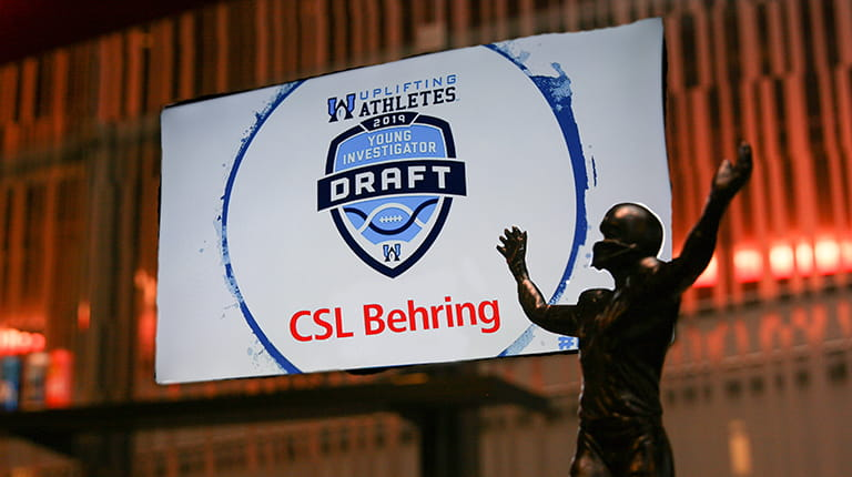 Uplifting Athletes Rare Disease Champion trophy in front of television screen with CSL Behring logo