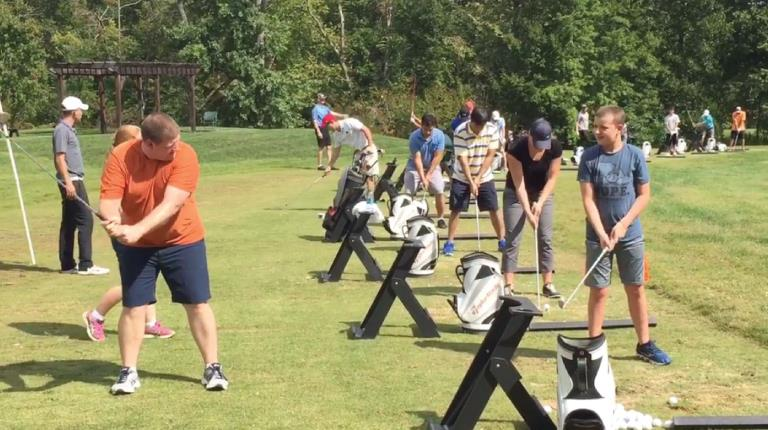 Father and son taking part in golf clinic