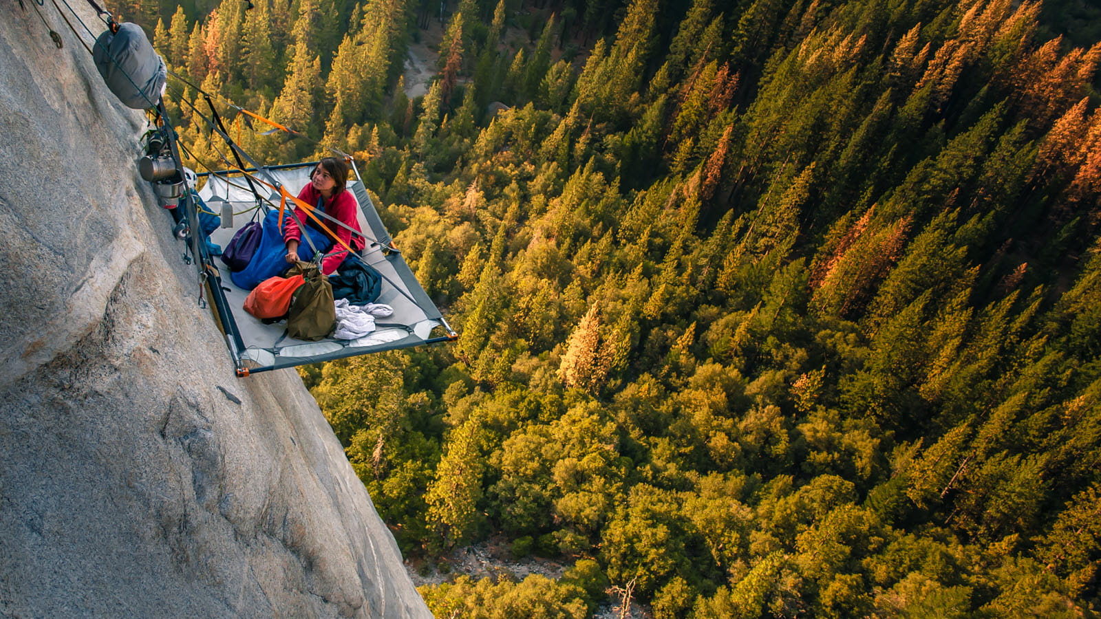 Climber takes a break from climbing hundreds of feet above the trees