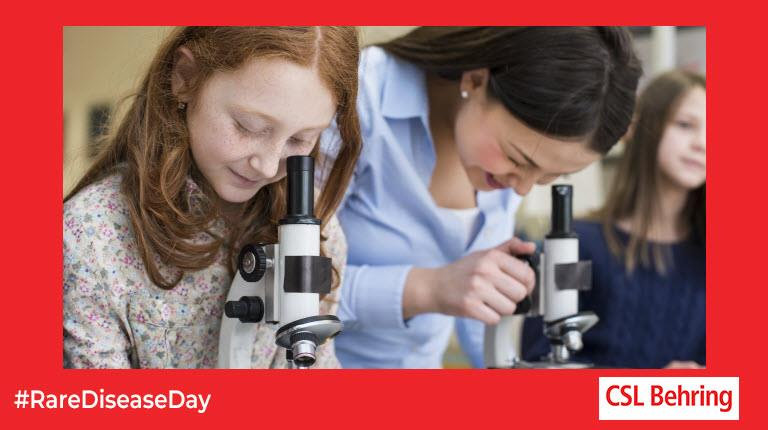 two girls looking into microscopes