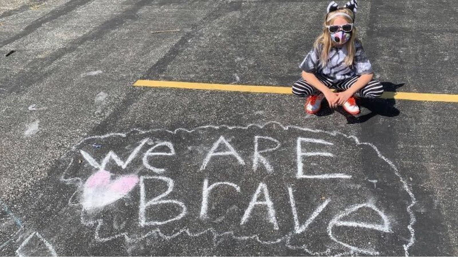 Little girl dressed in zebra attire with a chalk sign that says We Are Brave