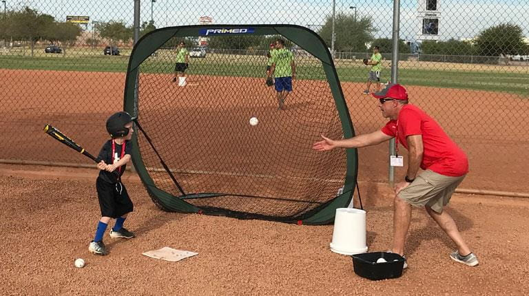 Small boy learning to hit a baseball