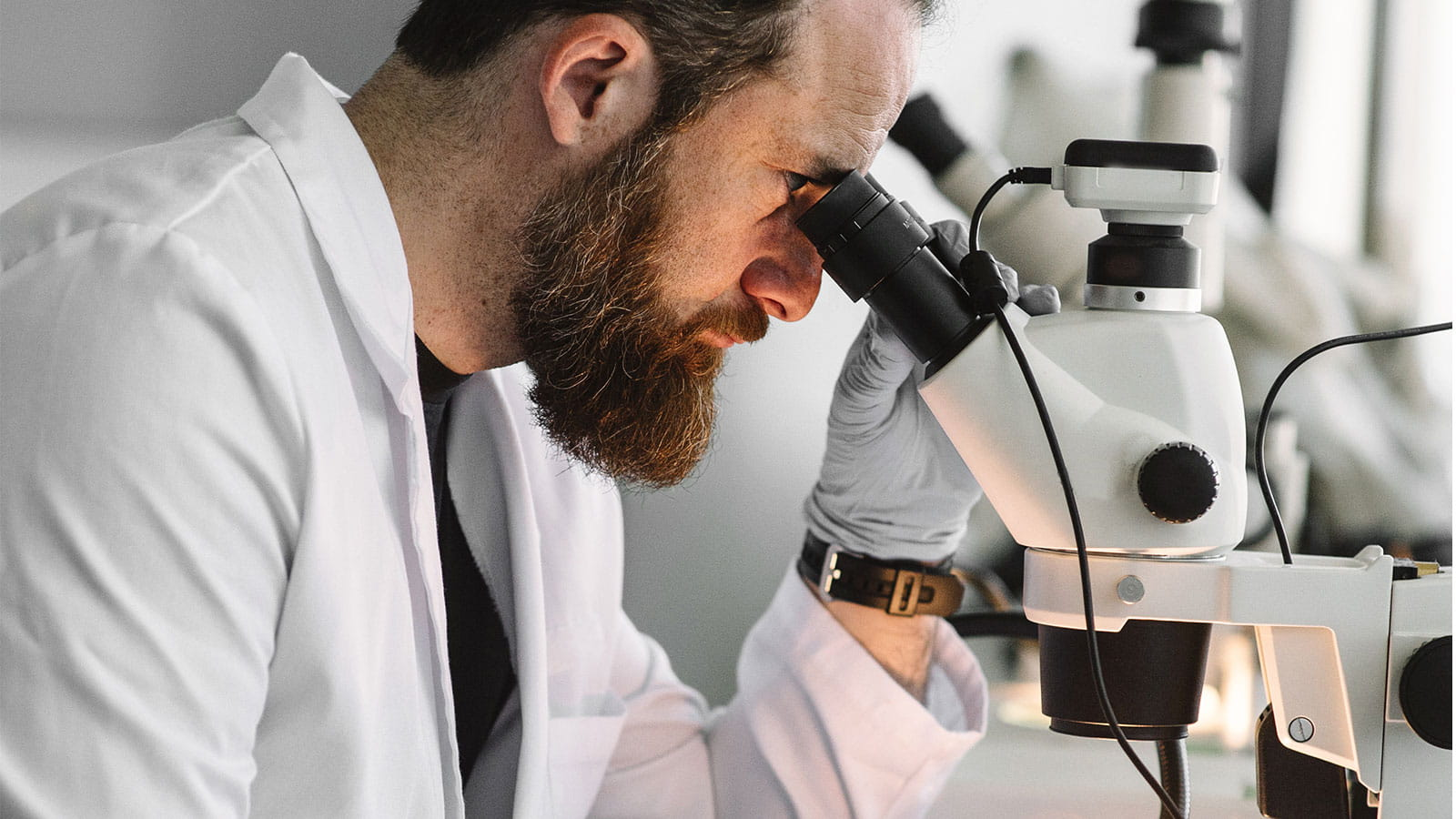 Man looking down into microscope