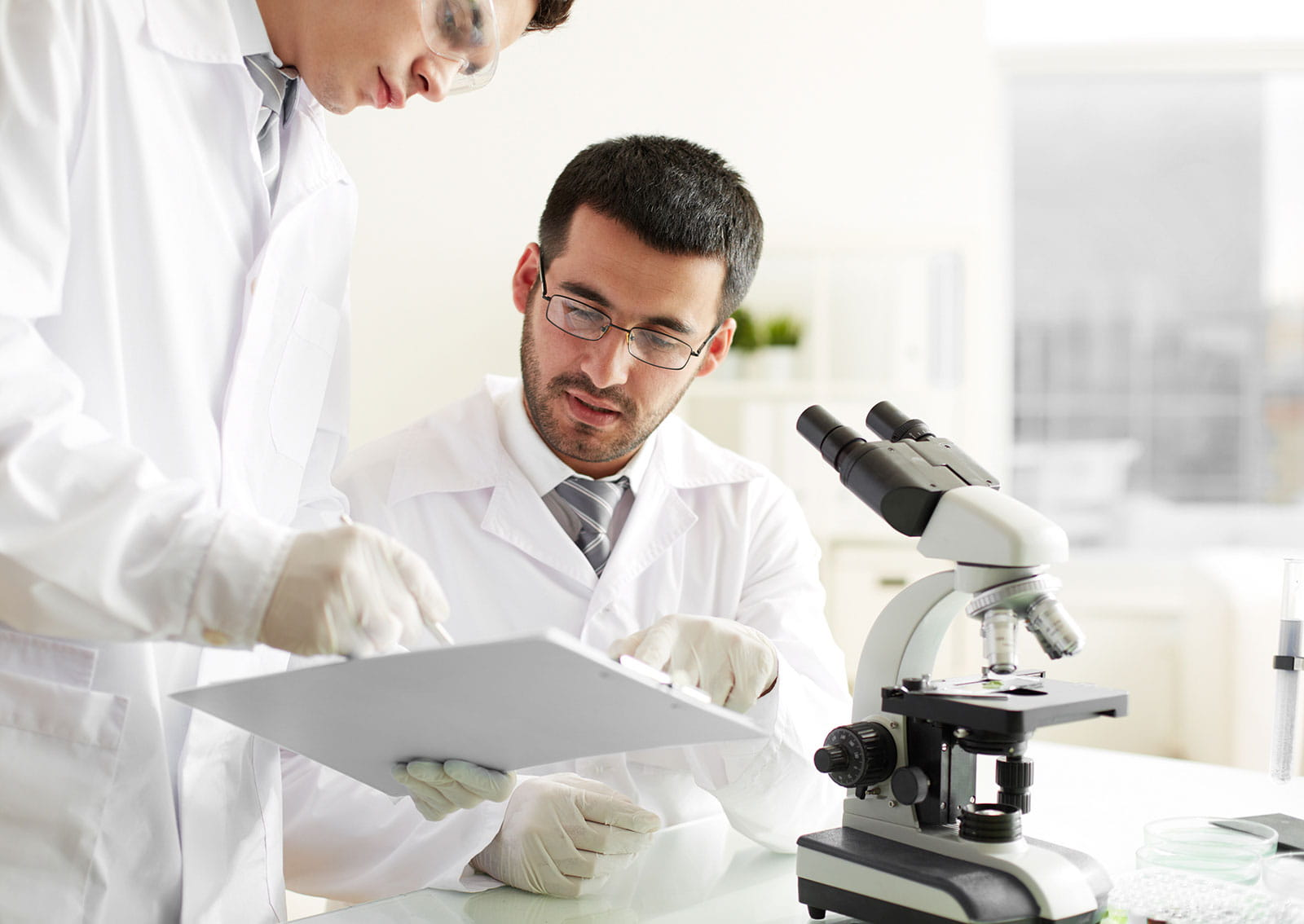 Two male scientist looking at a clipboard
