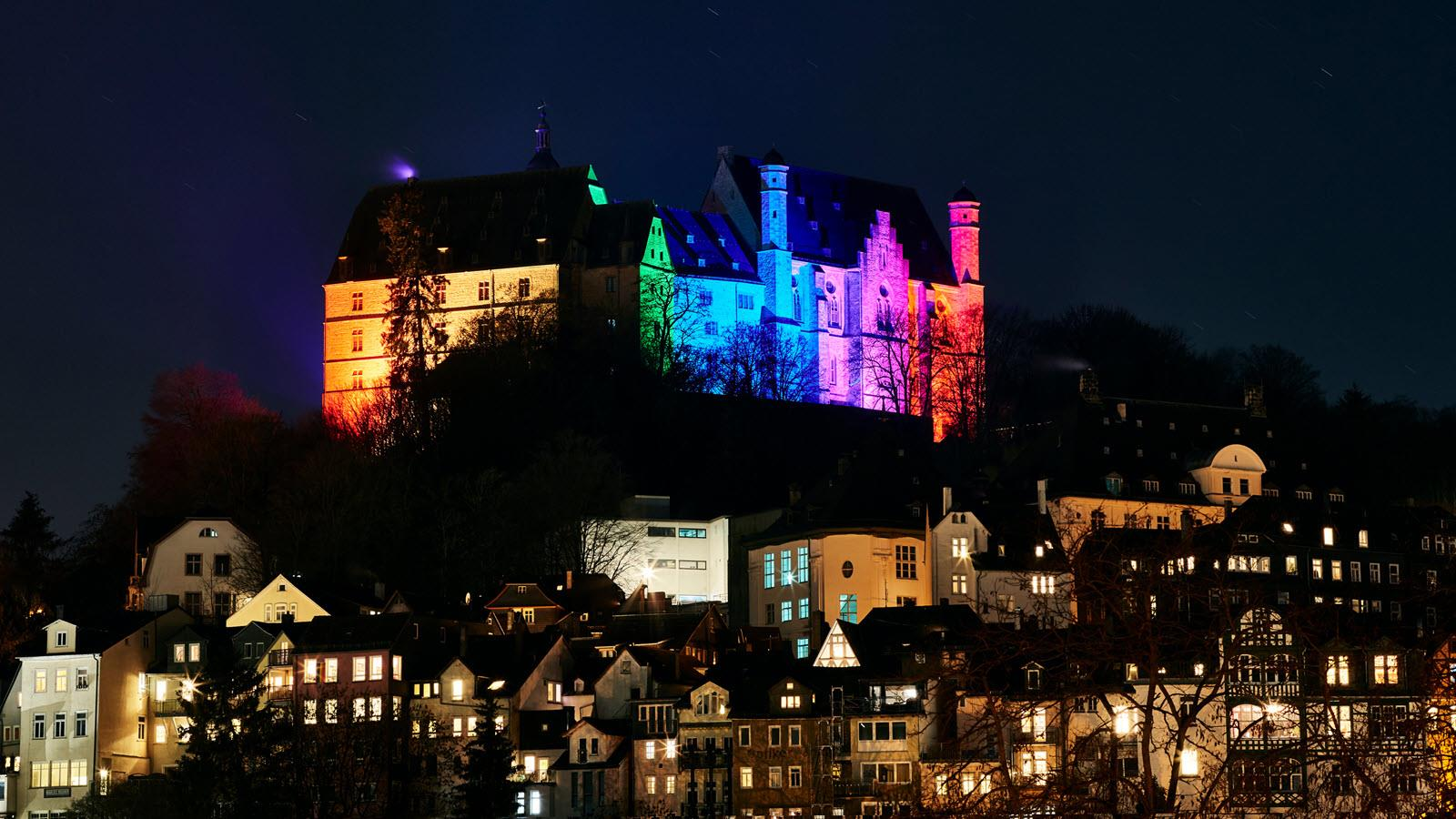 Marburg Castle lit up in yellow, green, blue and pink for Rare Disease Day