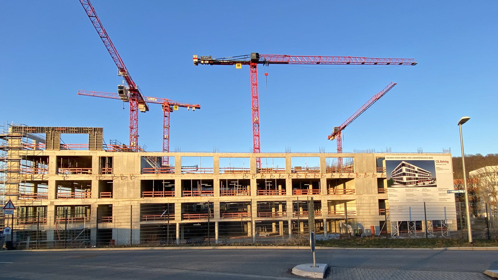 Several red construction cranes at work on upper floors of a new research building in Marburg, Germany