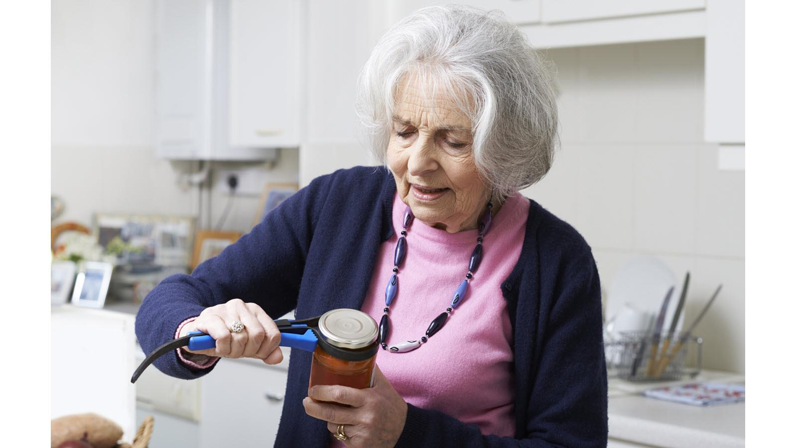 a gray haired older woman uses a tool to help open a jar