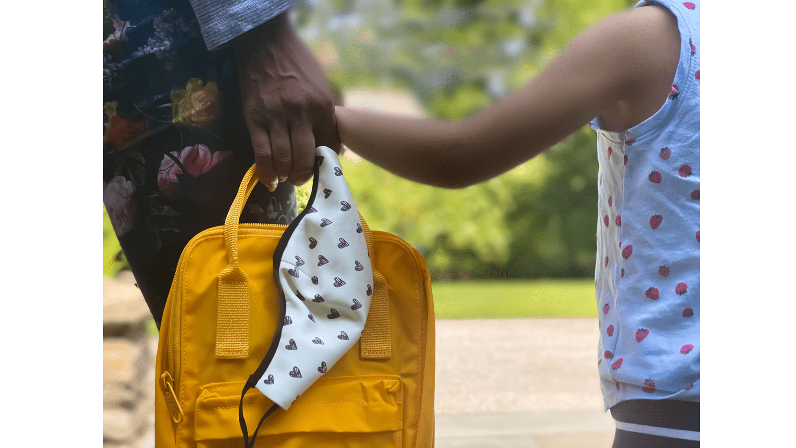 child holding mom's hand going back to school