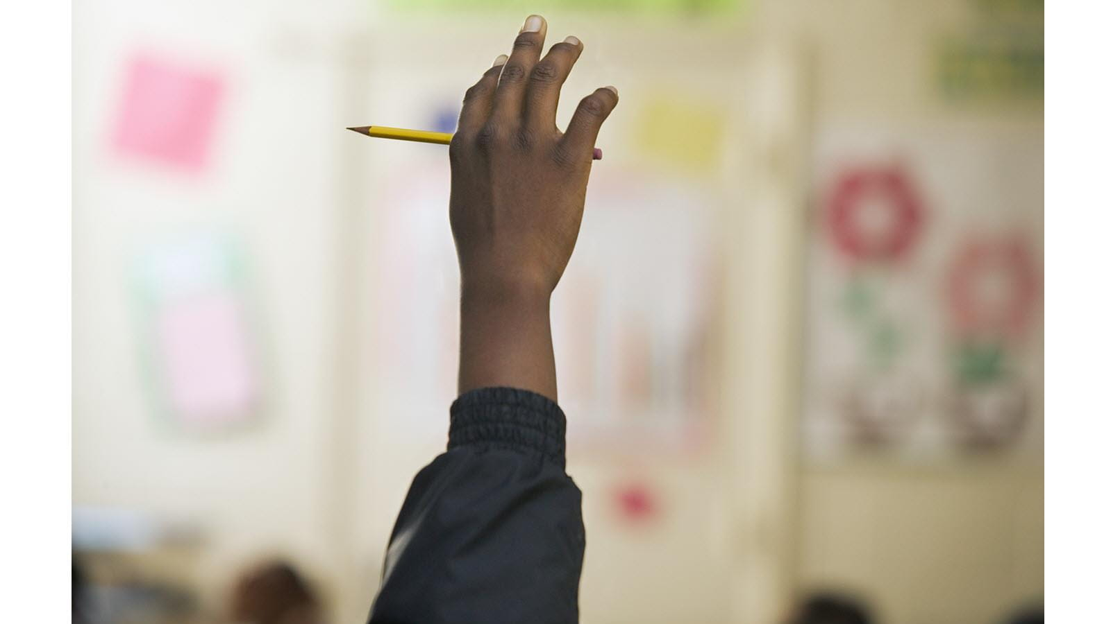 child's hand being raised in class