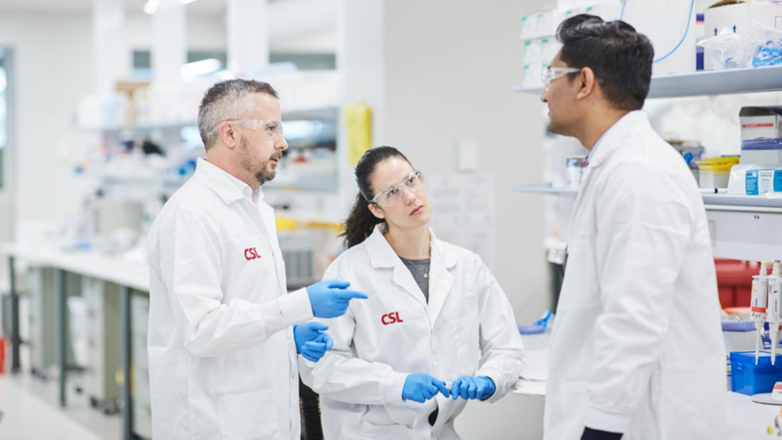 Two male and one female scientist talk in a lab environment