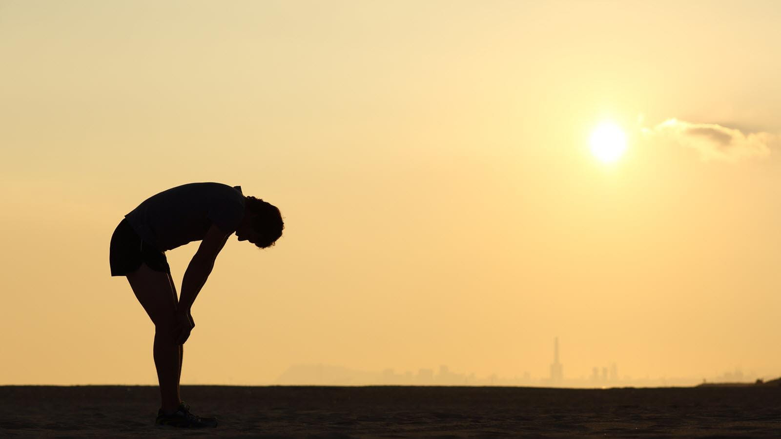 Exercising man doubled over under a hot sun