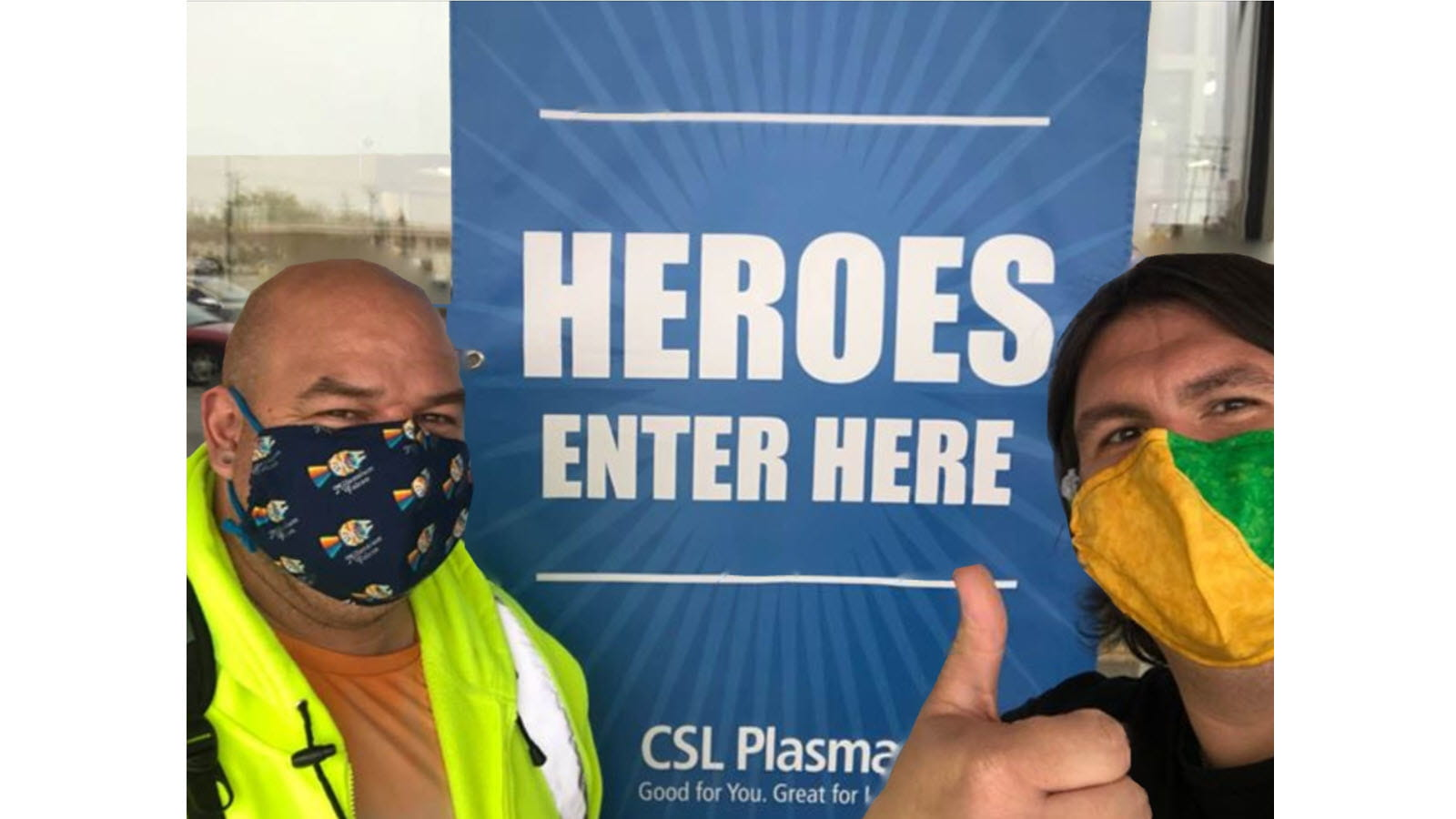 Two CSL Behring employees - Jason Tanner and Guy Redman - outside a CSL Plasma Center showing thumbs up