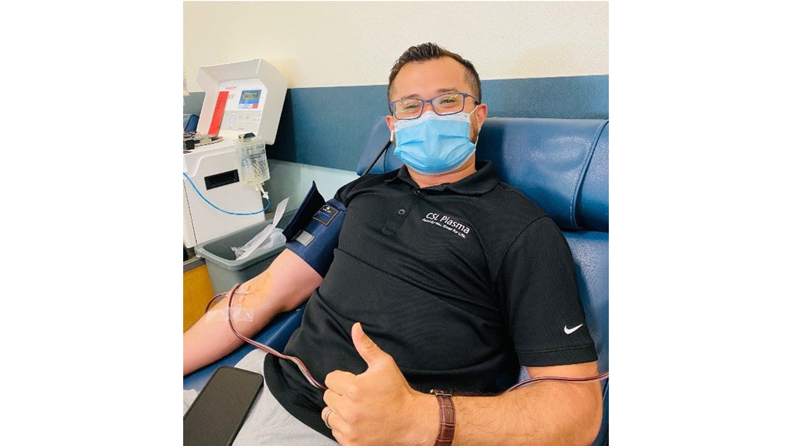 Jose Pineda gives a thumbs up sign while donating plasma