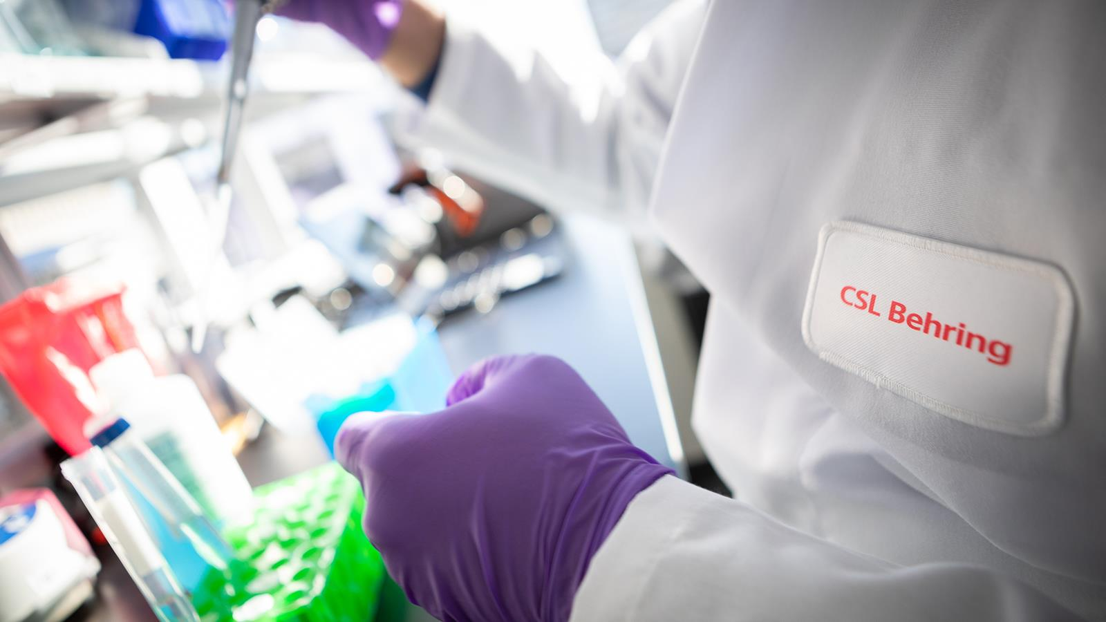 Gloved hands of a CSL Behring researcher in the lab
